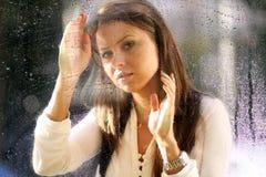 Młoda kobieta blisko okno po deszczu Obraz Stock