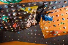 Młoda kobieta bouldering w wspinaczkowym gym Obrazy Stock
