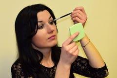 Młoda kobieta brunetka robi up powiekom Zdjęcie Royalty Free