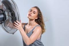 M?oda kobieta cieszy si? ch?odno wiatr od elektrycznego fan zdjęcia stock