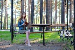 Młoda kobieta czyta książkę i relaksuje przy parkiem obraz royalty free