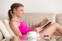Młoda kobieta czytelniczy towarowy katalog na kanapie w domu Zdjęcie Stock