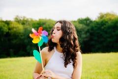 Młoda kobieta dmucha wiatraczek Obrazy Stock
