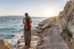 Młoda kobieta fotograf na skalistym seashore na wieczór Zdjęcia Royalty Free