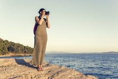 Młoda kobieta fotograf na skalistym seashore na wieczór Obrazy Stock