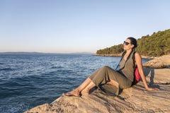 Młoda kobieta fotograf na skalistym seashore na wieczór Fotografia Stock