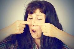Młoda kobieta gniesie krosty na ona nos Zdjęcia Royalty Free