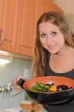 Młoda kobieta gotuje dennego jedzenie. Obrazy Stock