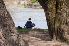 Młoda kobieta i jej pies relaksujemy blisko rzeki Obraz Stock