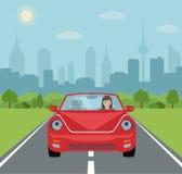 Młoda kobieta jedzie czerwonego samochód na miasta tle Zdjęcia Stock