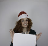 Młoda kobieta jest ubranym Santa kapeluszowego mienia pustego znaka Fotografia Stock