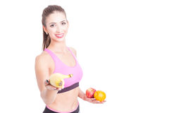 Młoda kobieta jest ubranym sportswear przy gym mienia owoc Zdjęcie Stock