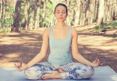 Młoda kobieta medytuje outdoors w wiosny lata parku Fotografia Stock