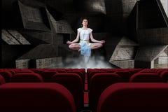 Młoda kobieta medytuje w powietrzu w 3d pokoju z pustymi kinowymi siedzeniami Obraz Stock