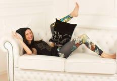 Młoda kobieta na kanapie Fotografia Royalty Free