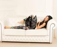 Młoda kobieta na kanapie Obrazy Stock