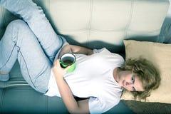 Młoda kobieta na kanapie w wczesnym poranku Zdjęcia Stock