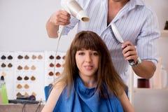 M?oda kobieta odwiedza m?odego przystojnego fryzjera m?skiego fotografia royalty free