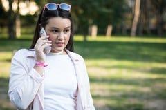 Młoda kobieta opowiada na smartphone outdoors w parku zdjęcie royalty free