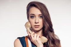 Młoda kobieta opowiada na starym moda telefonie Fotografia Stock