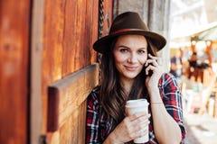 Młoda kobieta opowiada przy cel z kapeluszem obok starego drewnianego drzwi Fotografia Stock