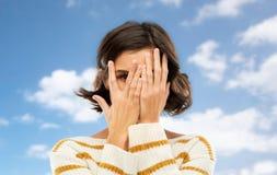 M?oda kobieta patrzeje jeden okiem przez ona palce zdjęcie royalty free