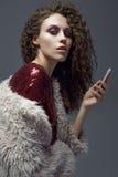 Młoda kobieta patrzeje w jego telefonie w studiu, Obraz Stock