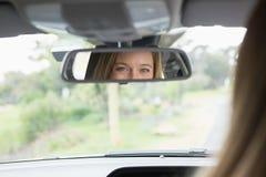 Młoda kobieta patrzeje w lustrze w kierowcy siedzeniu Obrazy Royalty Free