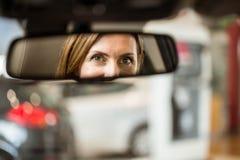 Młoda kobieta patrzeje w lustrze w kierowcy siedzeniu Zdjęcia Stock
