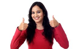 Młoda kobieta pokazuje aprobata gest przeciw bielowi obraz stock