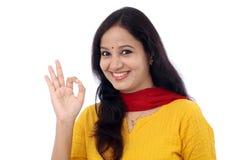 Młoda kobieta pokazuje OK znaka przeciw bielowi Obrazy Stock