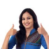 Młoda kobieta pokazuje thumbsup gest przeciw bielowi Fotografia Stock