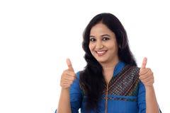 Młoda kobieta pokazuje thumbsup gest przeciw bielowi Obraz Stock