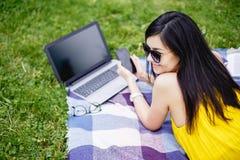 Młoda kobieta pracuje na laptopie w plenerowym Fotografia Royalty Free