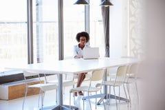 Młoda kobieta pracuje w pustym pokoju konferencyjnym Zdjęcie Stock