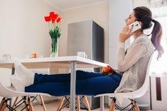 Młoda kobieta relaksuje i opowiada na telefonie w kuchni nowoczesna kuchnia projektu Obraz Stock