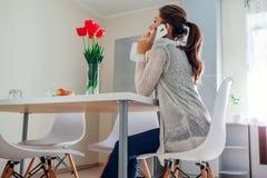 Młoda kobieta relaksuje i opowiada na telefonie w kuchni nowoczesna kuchnia projektu Obrazy Stock