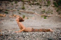 Młoda kobieta robi joga na skalistym seashore Oddolna obszycie psa poza Zdjęcia Stock