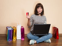 młoda kobieta robi zakupy online w domu Dziewczyna z torba na zakupy siedzi Obrazy Stock