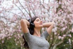 M?oda kobieta s?ucha muzyka na bezprzewodowych he?mofonach w parku z czere?niowego okwitni?cia drzewami zdjęcia royalty free