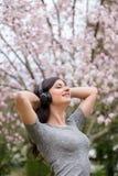 M?oda kobieta s?ucha muzyka na bezprzewodowych he?mofonach w parku z czere?niowego okwitni?cia drzewami fotografia stock