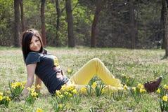 Młoda kobieta siedzi blisko daffodils Obrazy Royalty Free