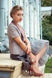 Młoda kobieta siedzi na krokach dom Zdjęcie Royalty Free