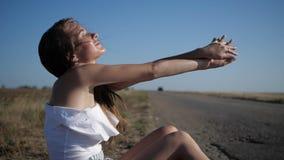 Młoda kobieta siedzi na polu zbiory wideo