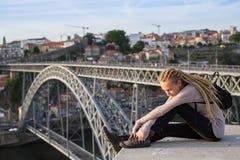 Młoda kobieta siedzi na tle most Dom Luis Mnie z dreadlocks, Porto, Portugalia Obraz Stock