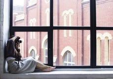 Młoda kobieta siedzi na windowsill z wielkimi okno i wp8lywy Fotografia Stock