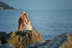Młoda kobieta siedzi z powrotem na dennym kamieniu Obraz Stock