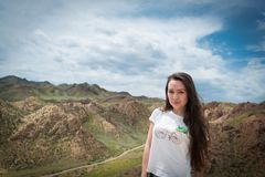 Młoda kobieta stojaki na tle z widokiem na górach fotografia stock