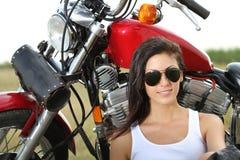 Młoda kobieta target1086_1_ blisko motocyklu Obrazy Royalty Free