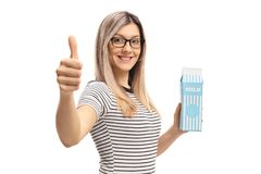 Młoda kobieta trzyma dojnego karton i robi kciukowi up podpisuje Fotografia Royalty Free